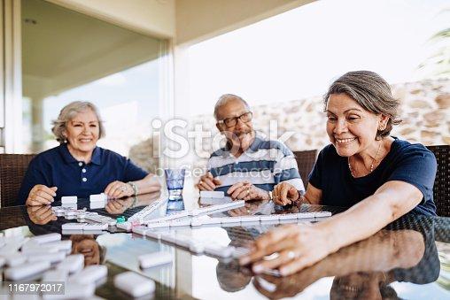 Latin seniors playing dominos at home