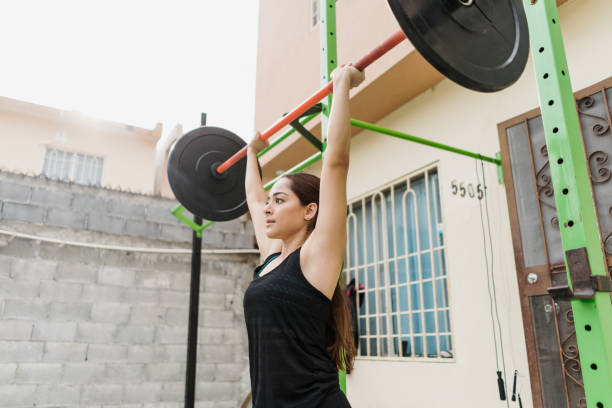 Latin sportswoman lifting bar with weights at home stock photo