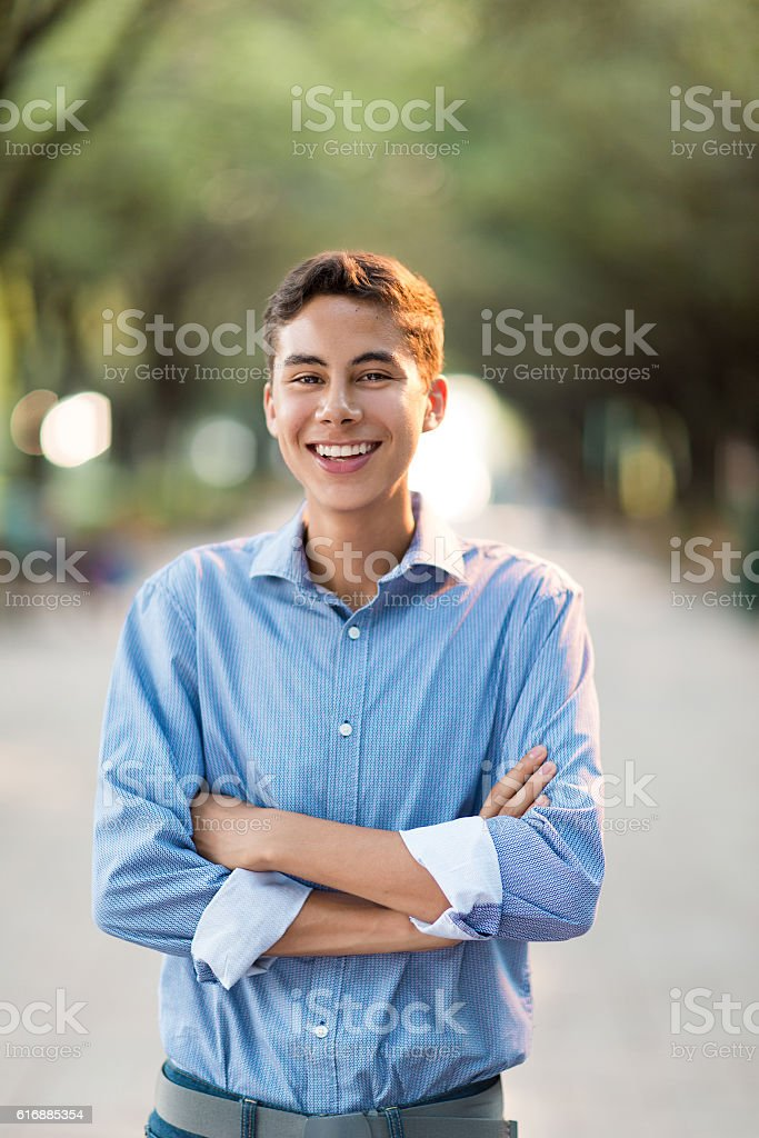 Latin Teenage Boy Standing With Arms Crossed And Smiling