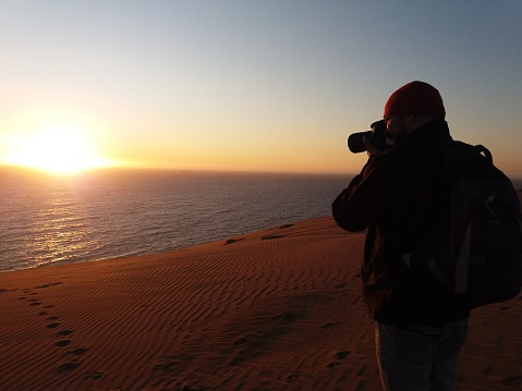 A latin tourist male / Photographer / Bedouin enjoying, relaxing and taking pictures in Reñaca / Concon's Sand dunes with a beautiful landscape view at sunset with a dramatic blue sky in Concon, Viña del Mar, Valparaiso, Chile.  Concon and Reñaca beach town are the most nearest towns, they are located in the north side of Viña del Mar - Valparaiso Bay, central Chile, just two hours driving from Santiago Capital by car, this area is most expensive and exclusive beach area around Chile.  Reñaca / Concón are a summer vacation area and receives a very large number of national and international tourists during the summer months. The tourist part of town is clustered around the main beach, and the lower part of the hill overlooking the beach is covered with residential buildings that sprawl up the hillside.