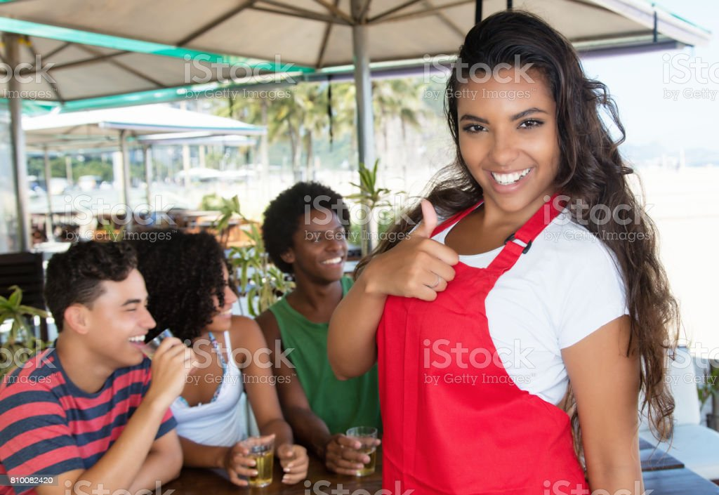 Latin waitress with guests in a bar showing thumb up stock photo