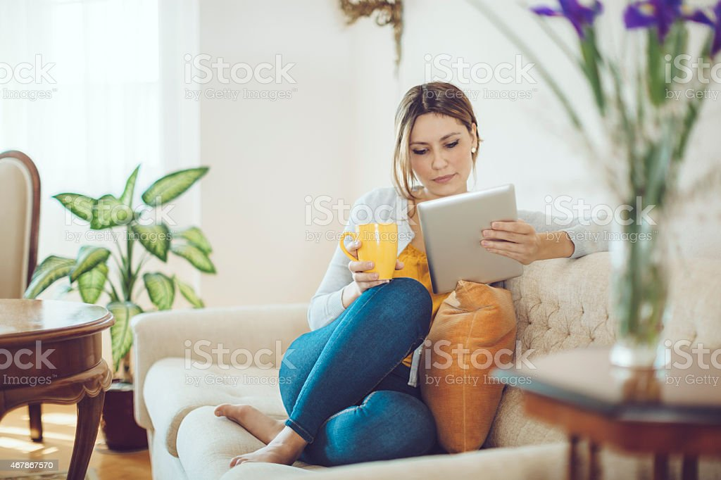 Latin woman drinking coffee and reading a tablet stock photo