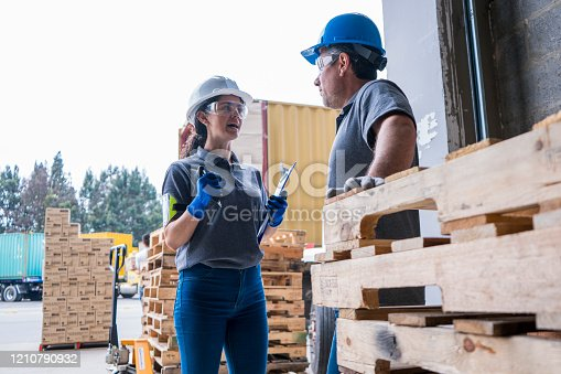 Latin woman of approximately 30 years with a prtection helmet and glasses dressed in the company's uniform is in the facilities of the large factory with a blue notepad discusses work related issues with her partner, also a uniformed Latino man with safety helmet
