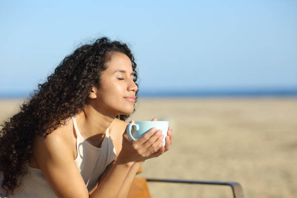 latin woman enjoying a cup of coffee on the beach - vacations food stock pictures, royalty-free photos & images