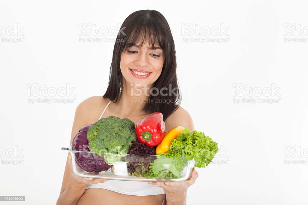 Latin Woman Holding A Tray Of Vegetables stock photo