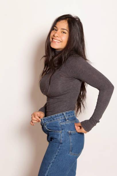 lateinische frau in baggy-hosen, drinnen. - damen sporthose übergröße stock-fotos und bilder