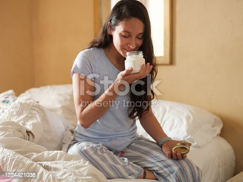 A young latin woman sitting on her bed with her pajamas on and smelling a jar with lotion.