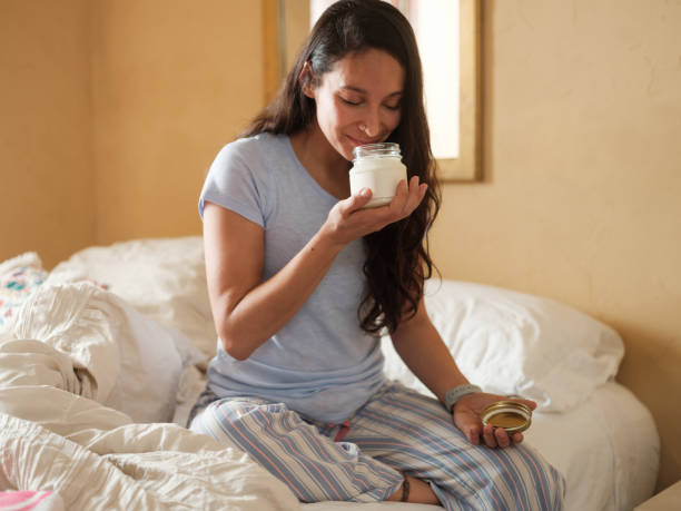 Latin woman in bed smelling a jar of lotion stock photo