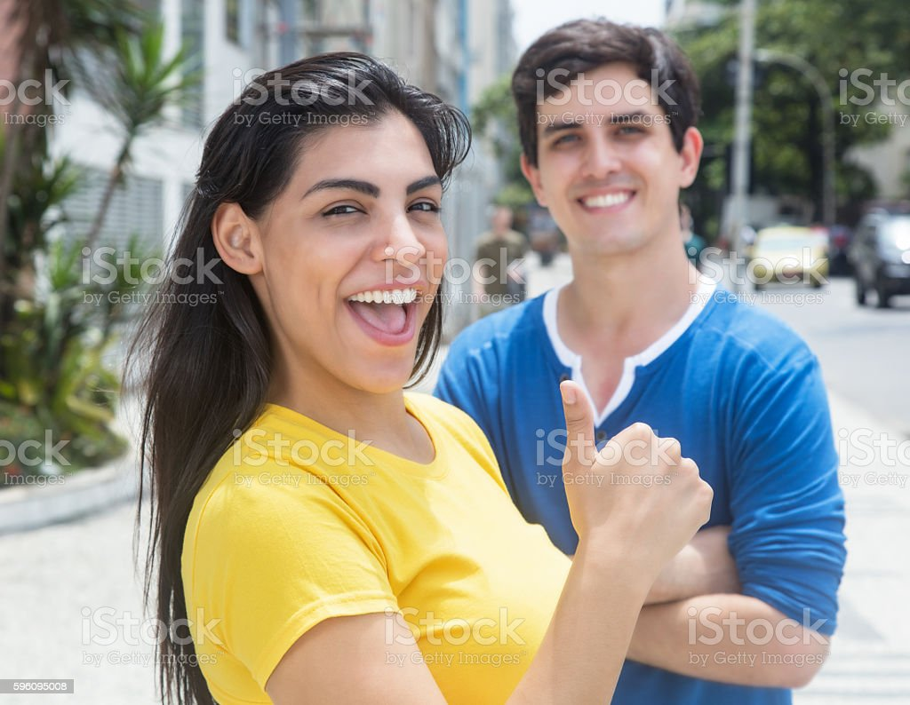 Latin woman in yellow shirt showing thumb with caucasian friend royalty-free stock photo