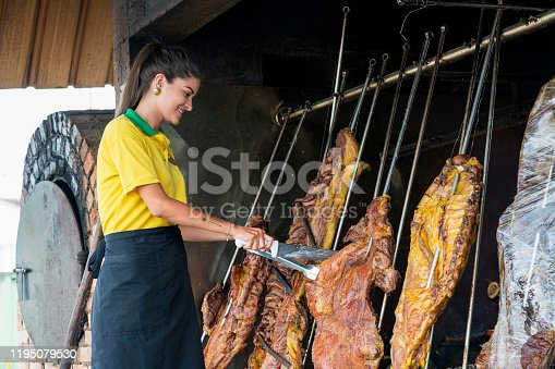 Latin woman of approximately 29 years of age employed at a typical meat expert restaurant called mamona called the huge barbecue where the meat is prepared to start slicing it