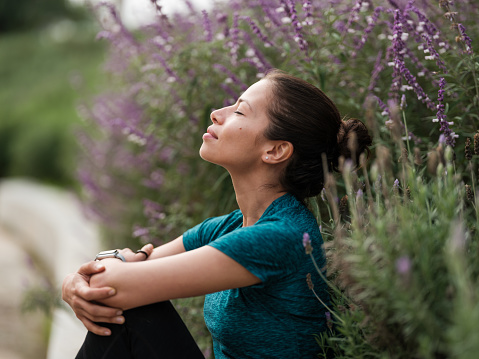 A latin woman sitting with her eyes closed and relaxing next to some flowers.