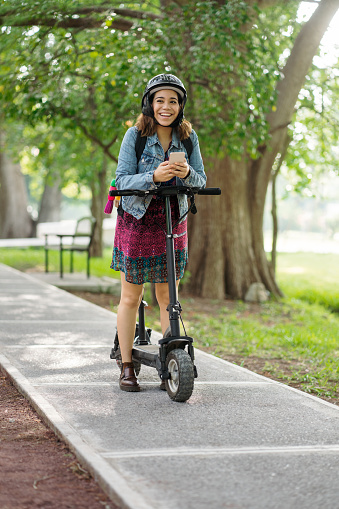 A young latin woman wearing a helmet, standing with a motorized scooter and smiling away with her phone on her hand.