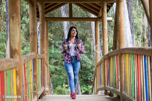 Latin woman with black hair, is in the middle of a forest surrounded by nature. She walks calmly and happily, with a backpack on her back, crossing a bridge