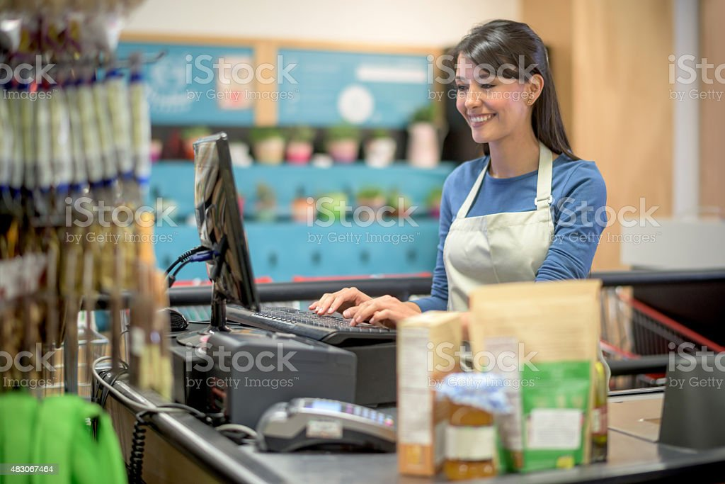 Latin woman working at a grocery store stock photo
