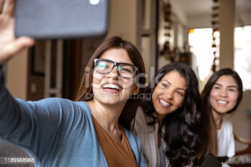 Three latin hispanic women friends at home spending some time break from studying chatting and on social media.