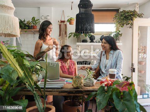 Beautiful latin women discussing at a table in a plant and pots shop.