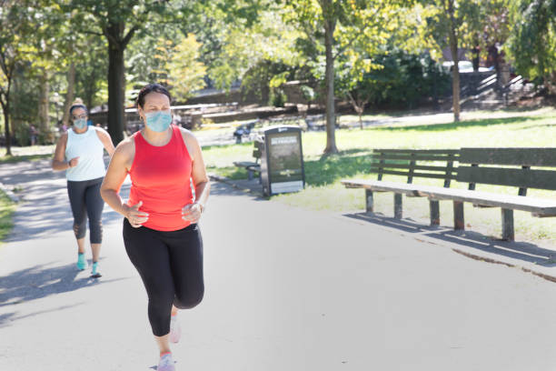 Latin women jogging outside in the park using mask