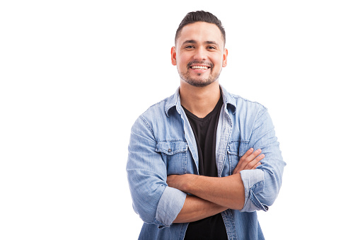 Handsome young Hispanic guy smiling with his arms crossed against a white background