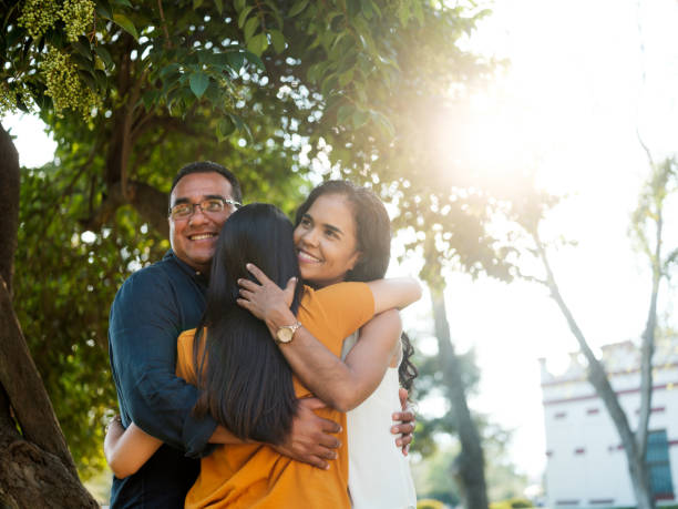Latin young woman hugging her parents stock photo