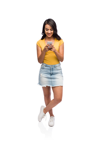 Full body shot of latin woman texting on her phone with one leg crossed over the other.