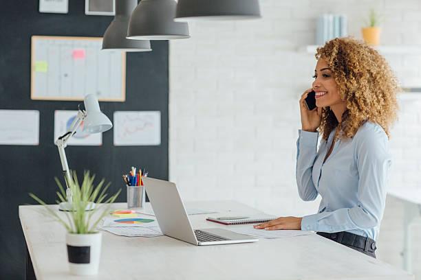 latina donna d'affari lavoro nel suo ufficio - owner laptop smartphone foto e immagini stock