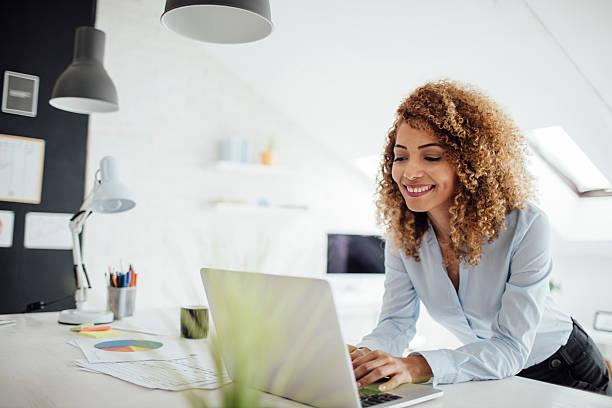 latina donna d'affari lavoro nel suo ufficio. - owner laptop smartphone foto e immagini stock