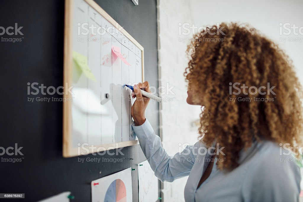 Latina Businesswoman Writing Schedule. stock photo