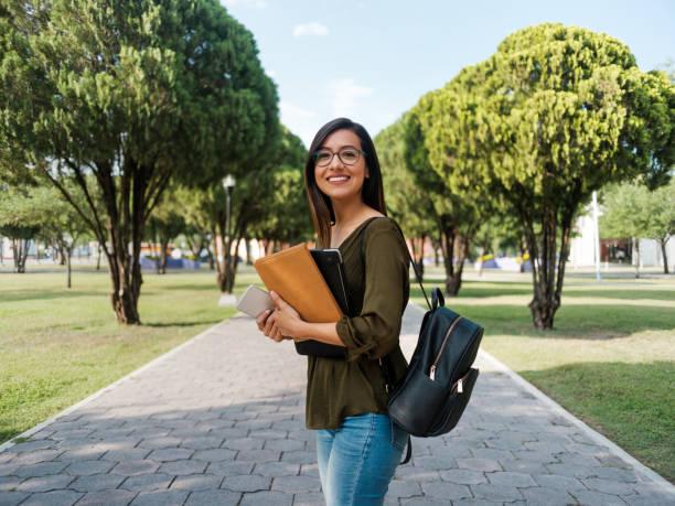 latina universitaria mirando a la cámara con una sonrisa - estudiante fotografías e imágenes de stock