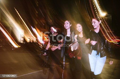 A group of young Hispanic women enjoy an evening out on the town in downtown Los Angeles, California.  They walk the streets of downtown LA, having a fun time.  Long exposure with blurred motion.