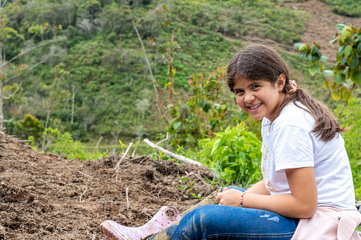latina girl sitting in a rural scene resting and enjoying a day in the countryside