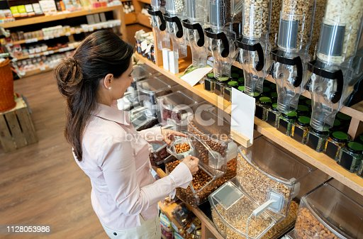 Latina merican adult woman buying dried fruits by bulk smiling