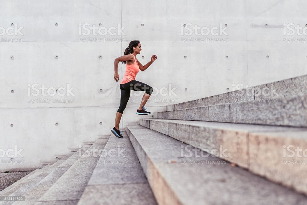 latina sports woman running up outdoor stairway in berlin stock photo