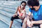 latina sportswoman and bearded sportsman checking smartwatch after running