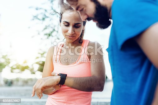 istock latina sportswoman and bearded sportsman looking together on smartwatch 635852662