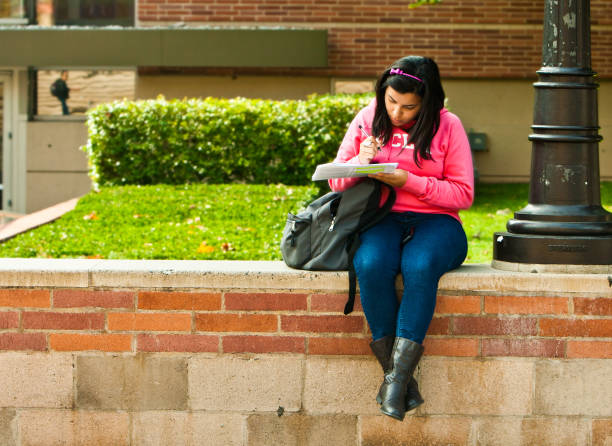 Latina University Student Studying Between Classes On Campus Los Angeles, USA - October 24, 2011: A young Hispanic girl studies on campus at UCLA as part of her educational development for the future. ucla medical center stock pictures, royalty-free photos & images