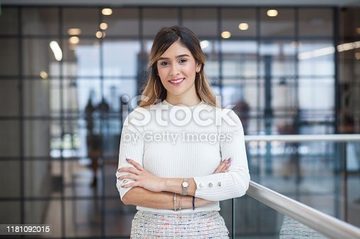 Executive Latin woman with long brown hair and white skirt and gray skirt with an approximate age of 28 is crossed arms and smiling at the camera with a half-sided stance in one of the corridors of the company for which she works next her a silver railing