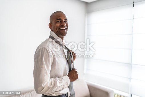973213156istockphoto Latino afro man getting dressed at home portrait 1130471944