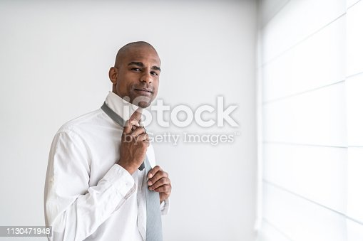 973213156istockphoto Latino afro man getting dressed at home portrait 1130471948