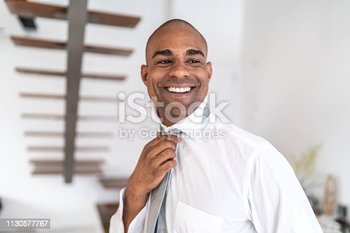 973213156istockphoto Latino afro man getting dressed at home portrait 1130577767