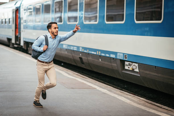 Latino businessman is late for the train stock photo