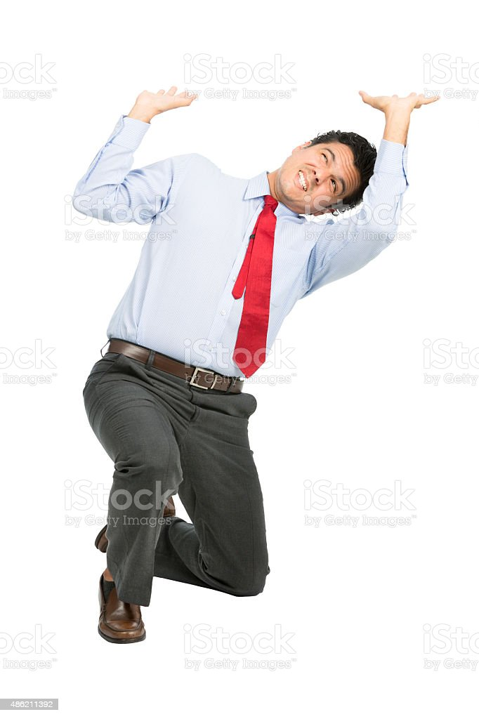 Latino Businessman Under Heavy Pressure Pushing stock photo