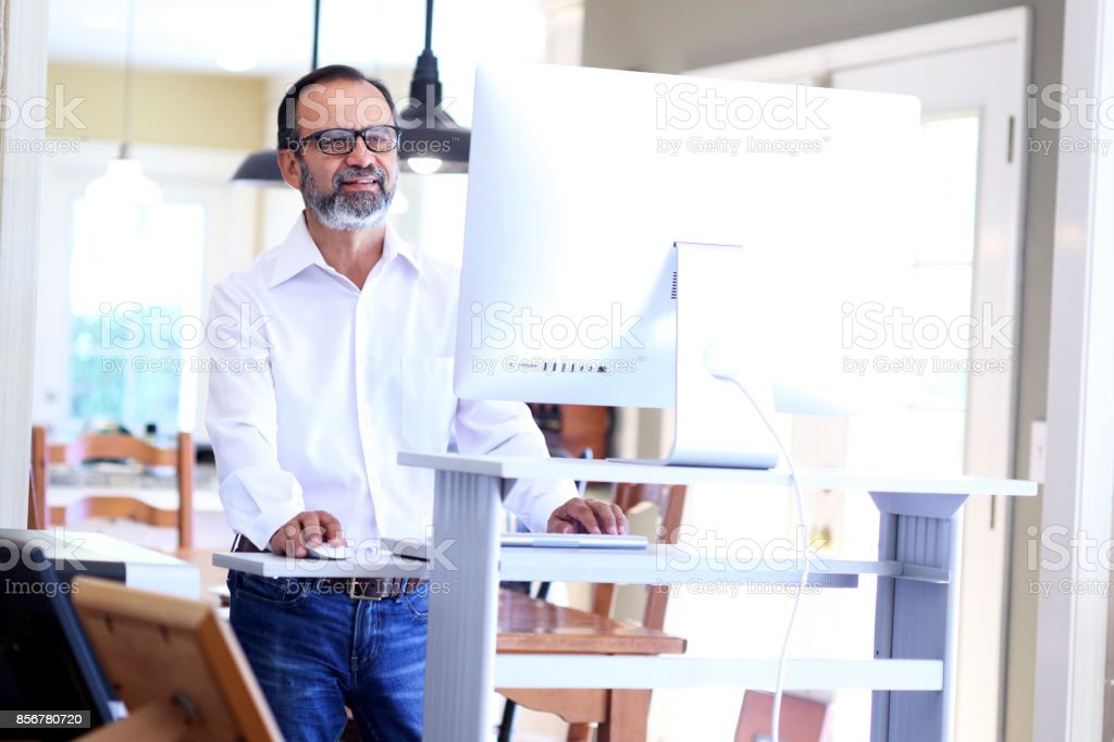 Latino Businessman Works At Standing Computer Desk At Home stock photo
