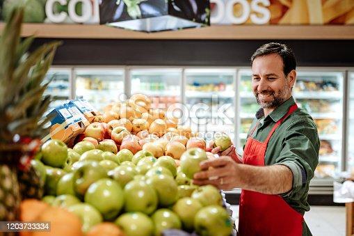Portrait of mature employee in supermarket