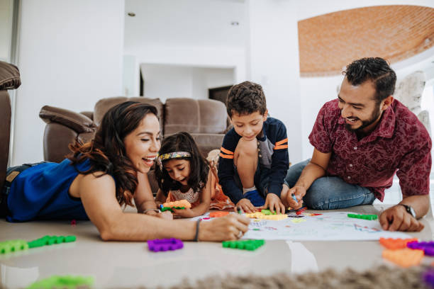 Latino family enjoying being together at home and playing with kids. stock photo