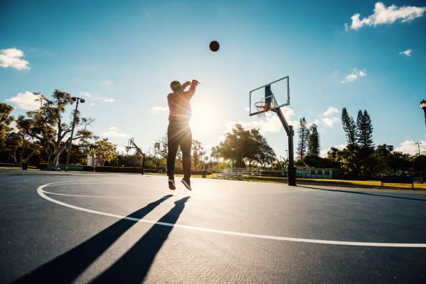 Latino Kerl schießen Basketball auf dem Platz in den USA im Sommer – Foto