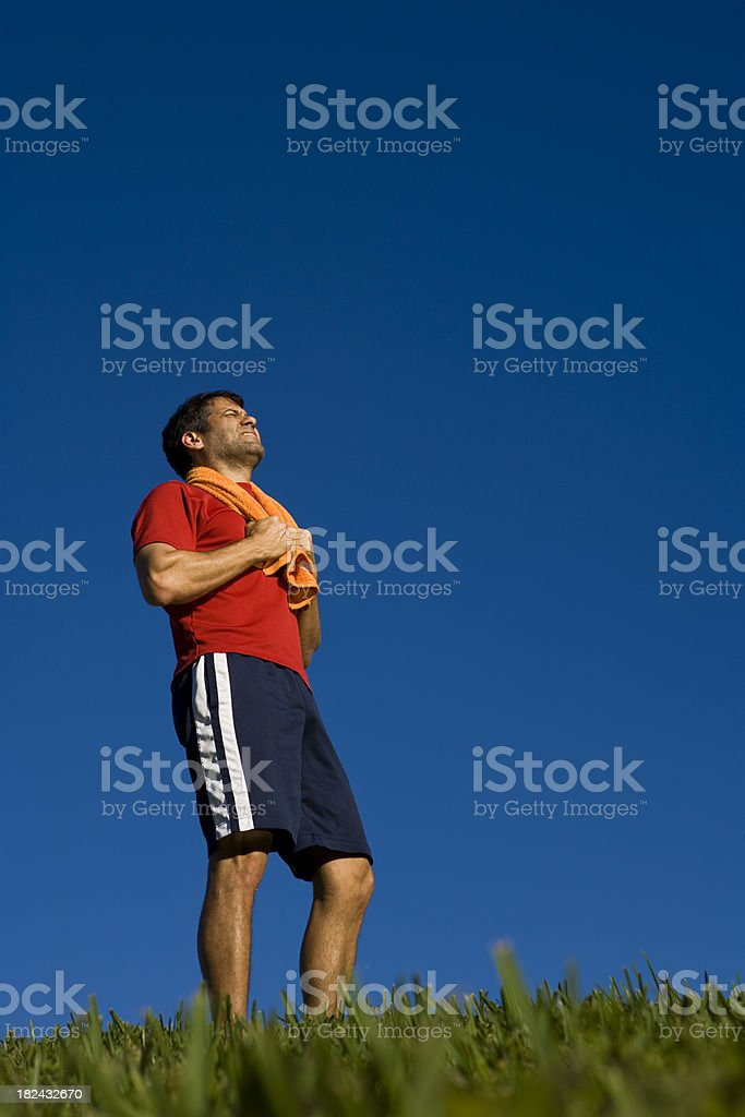 Latino male athlete with towel and looking up royalty-free stock photo