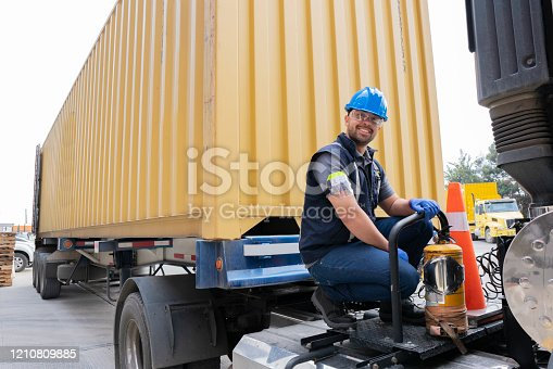Latin man of approximately 30 -39 years old dressed in a uniform of the company for which I work with his safety equipment as a helmet, glasses is on the mootra part of the truck of the company fixing it while looking at the camera