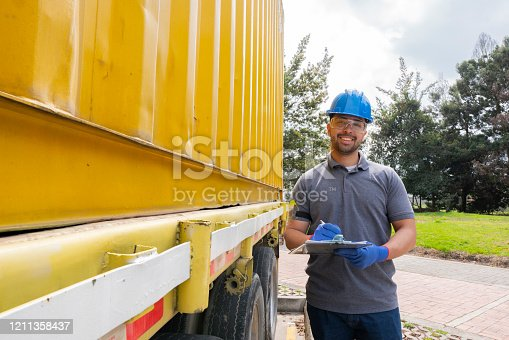 Latin man of approximately 30 -39 years old dressed in a uniform of the company for which I work with his safety equipment as a helmet, glasses standing facing forward while holding in his hands a notepad where he carries the data of the company next to it we observe a big truck of the company in the transport the merchandise