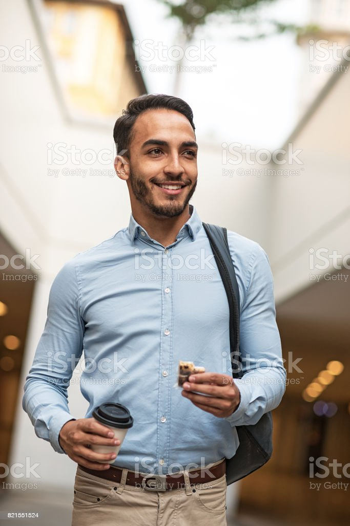 Latino man going to work and eating chocolate protein bar stock photo