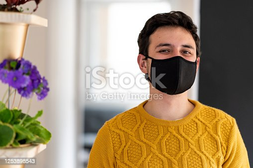Latino man of average age of 25 years dressed informally is in the living room of his house with his black face mask looking at the camera while he is quarantined by the covid- 19